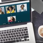 a laptop open with a group video call besides a cup of coffee