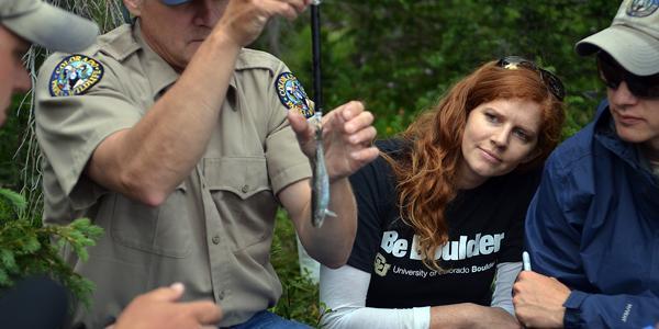 Thumbnail of Jessica Metcalf watching Harry Crockett weigh a cutthroat trout.