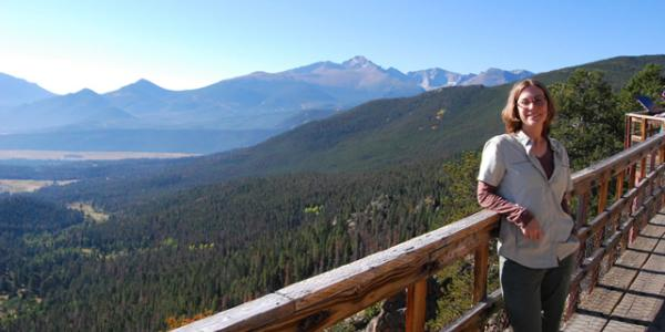 Orlofske standing on bridge overlooking mountain view