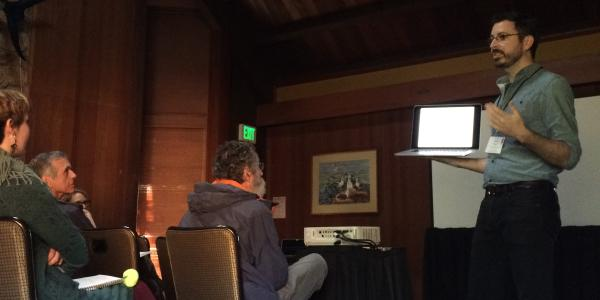 despite a power outage, Scott Taylor presents to a room of ASN members. Scott holds his laptop up for the crowd