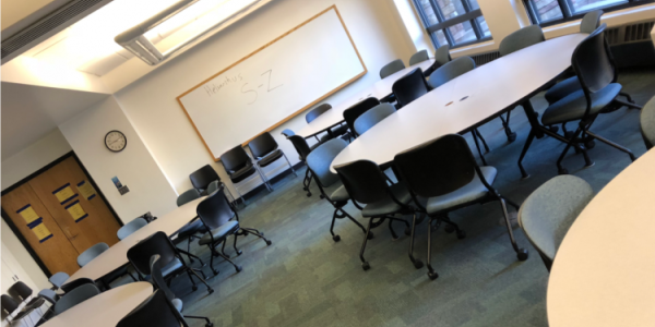 a tilted angle shot of an empty classroom with large circular desks and chairs