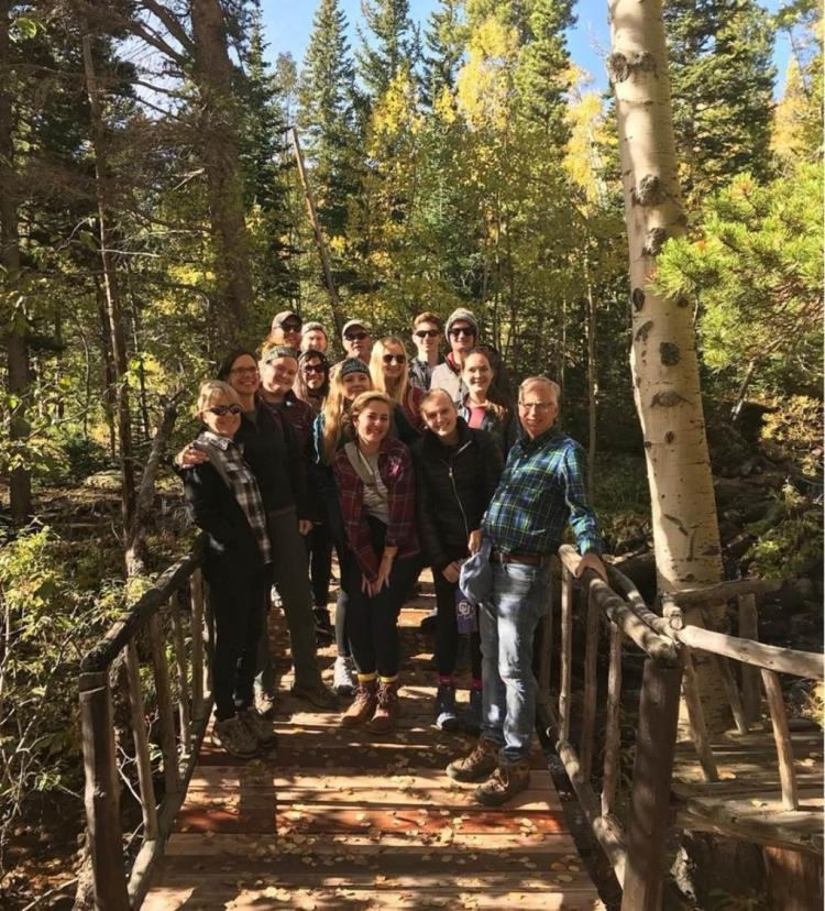 Mike breed with students on a wooded bridge. Aspen trees in background, the class is on a hike
