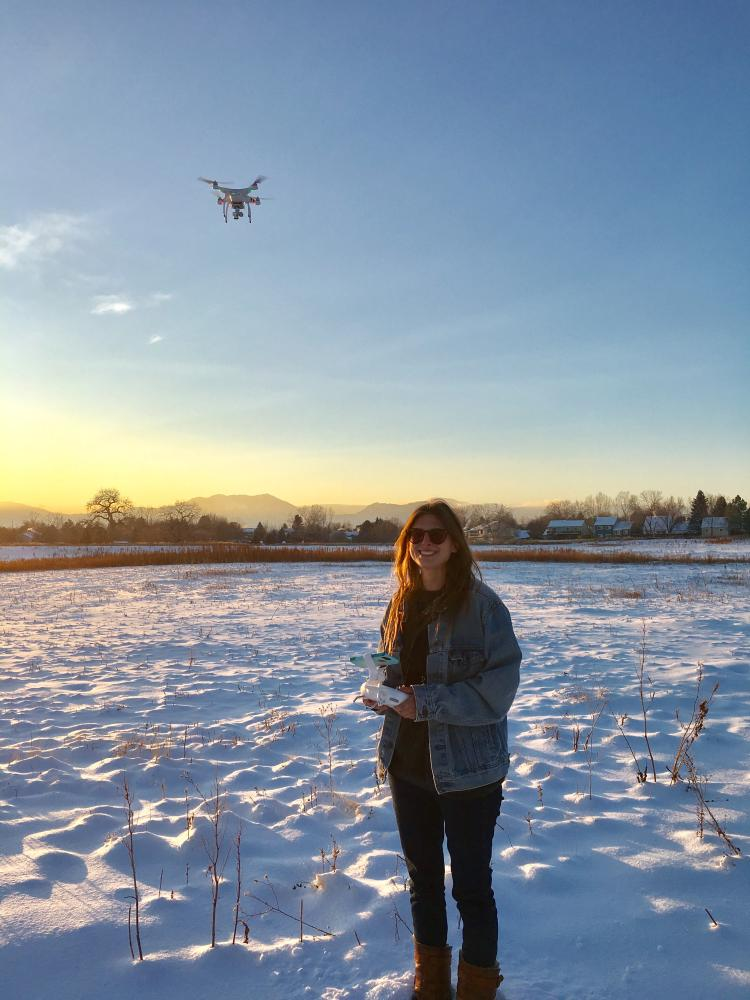 Coohill pilots a drone over a snowy field.