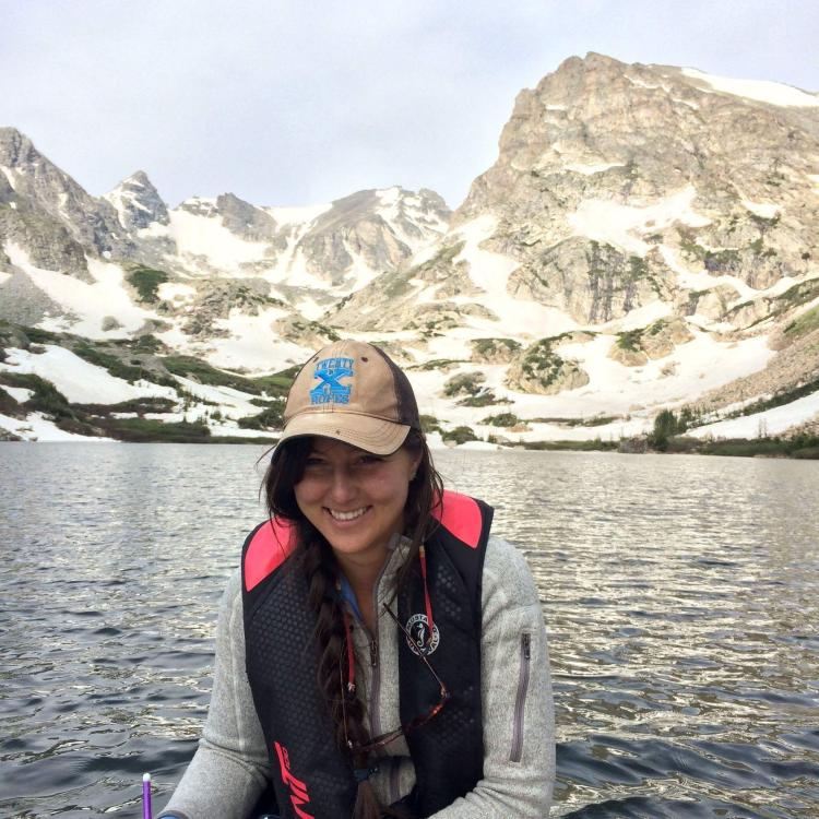 Loria smiles in front of a chilly alpine lake.