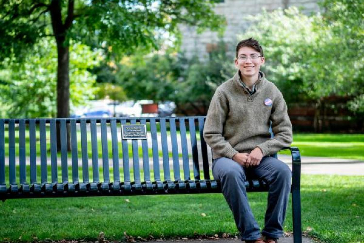 lior sitting on a park bench, greenery in background