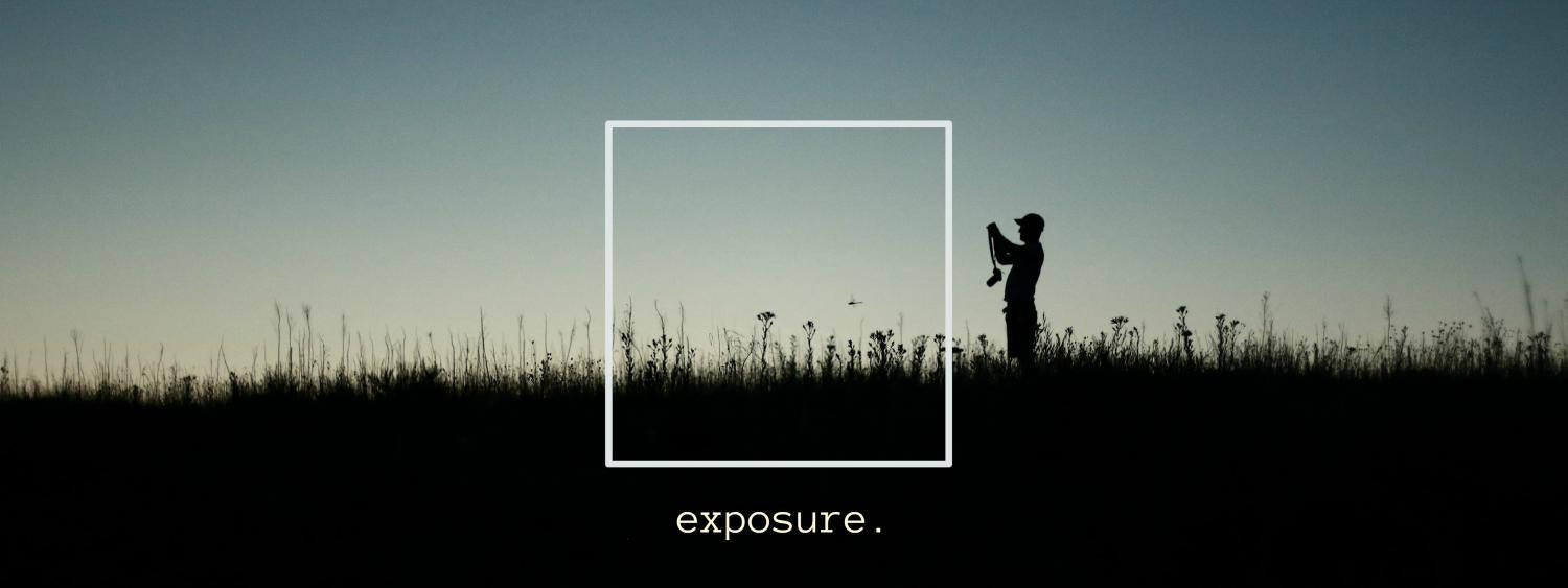 A silhouetted photographer in a grassy field is depicted in a banner for the Exposure project.