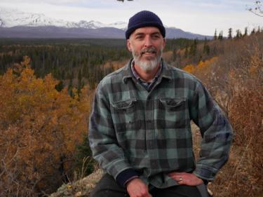 Andrew McAdam smiles with trees and mountains behind him.