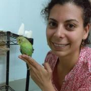 Medina-García poses with a budgerigar at the Wright Behavior Lab.