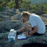 johanne conducting research on a rocky outcrop