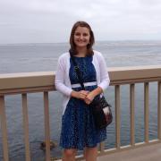 Amedee standing on a pier overlooking the ocean