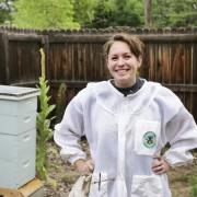 rachel stands in a bee suit, several bee hives in out of focus background