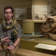 student discusses methods of sucess in front of large dinosaur skull