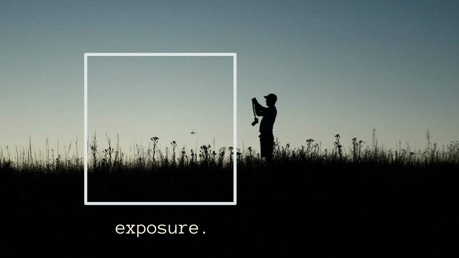"""The silhouette of a photographer stands in a field of tall grass captioned with """"exposure."""""""