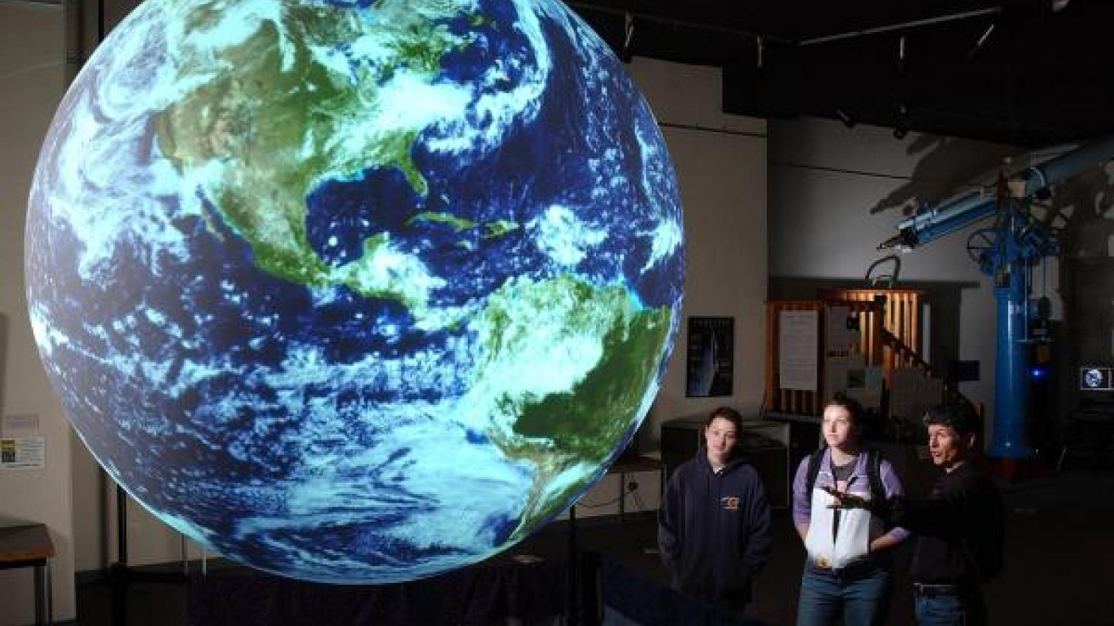 students stand behind a projection of the globe