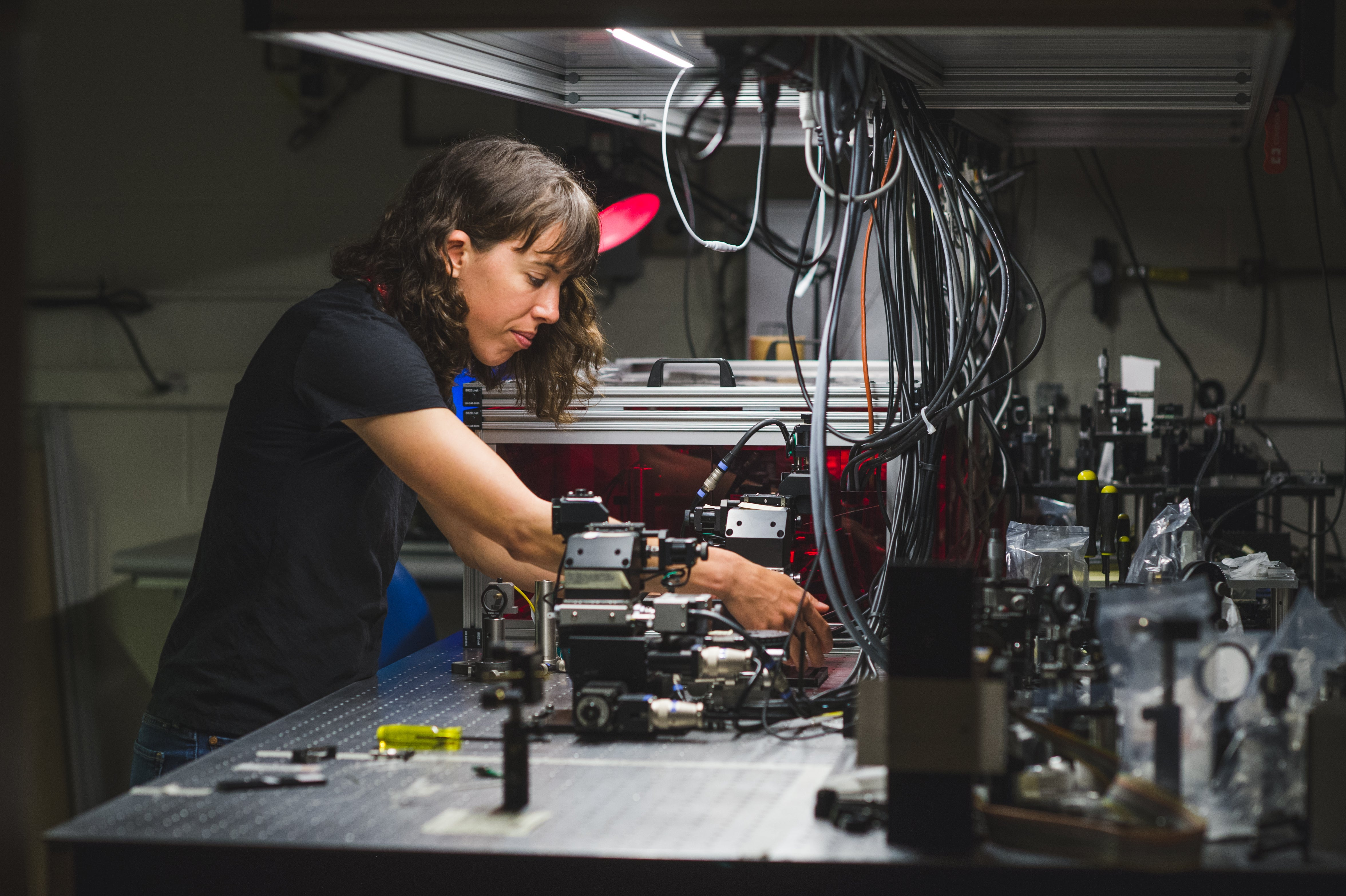 A grad student works on an optical project in her lab.