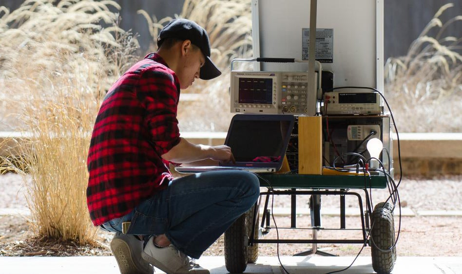 A student takes down measurements from his solar cart outside the Engineering Center.