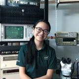 Giselle Koo sits in a lab filled with RF equipment