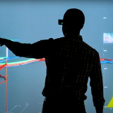 Silhouettes of Hodge and a colleague discussing data on a wall-sized screen at NREL