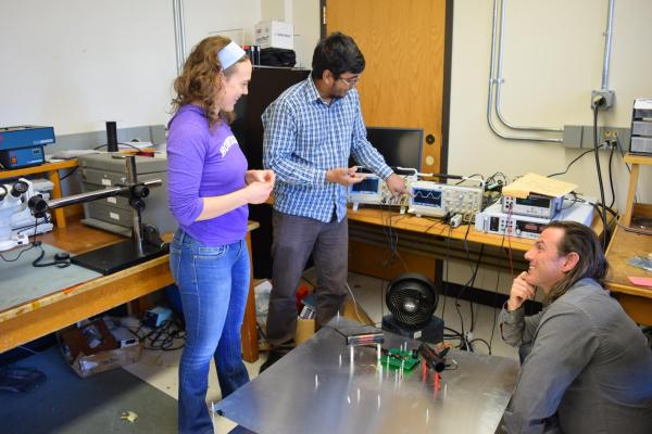 Three students discuss their project in the power electronics lab