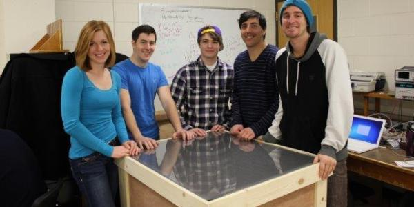 A team poses with their prototype in the senior design lab