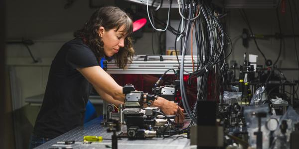A grad student works at an optics table in her lab.