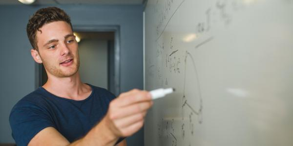 A grad student writes an equation on a whiteboard in his lab.