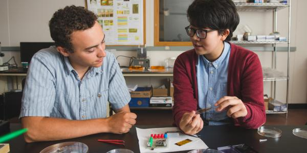 Two students discuss a project in their lab.
