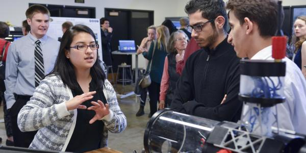 A student explains her project to visitors at the 2017 ECEE senior design expo.
