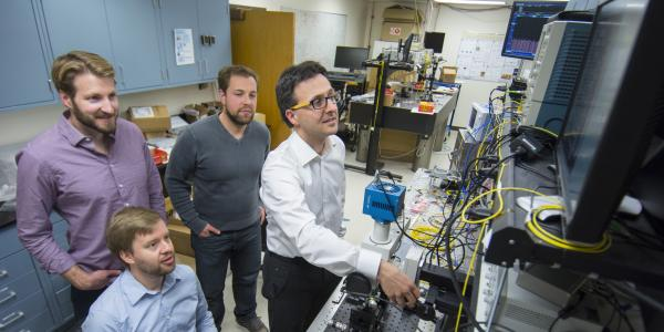 Milos Popovic with graduate students in their optics and nanotechnology lab