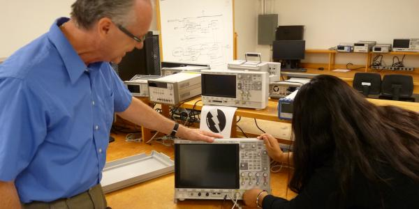 A representative from Keysight helps a ECEE student set up a donated oscilliscope