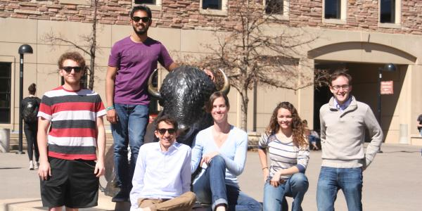 The members of Ocean's 7 gather for a team photo by the Folsom Field buffalo statue.