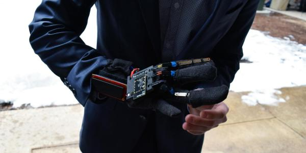 A team member shows off the GMA glove during the ECEE senior design projects expo
