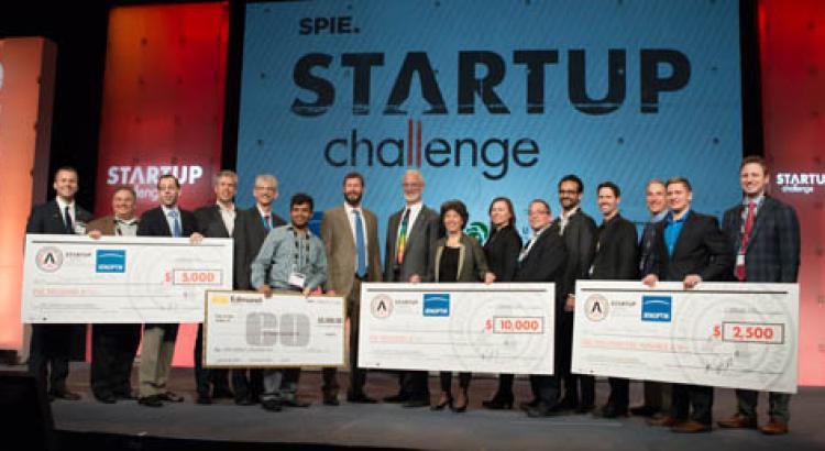 Leslie Kimerling accepts a novelty check on-stage at the SPIE Startup Challenge