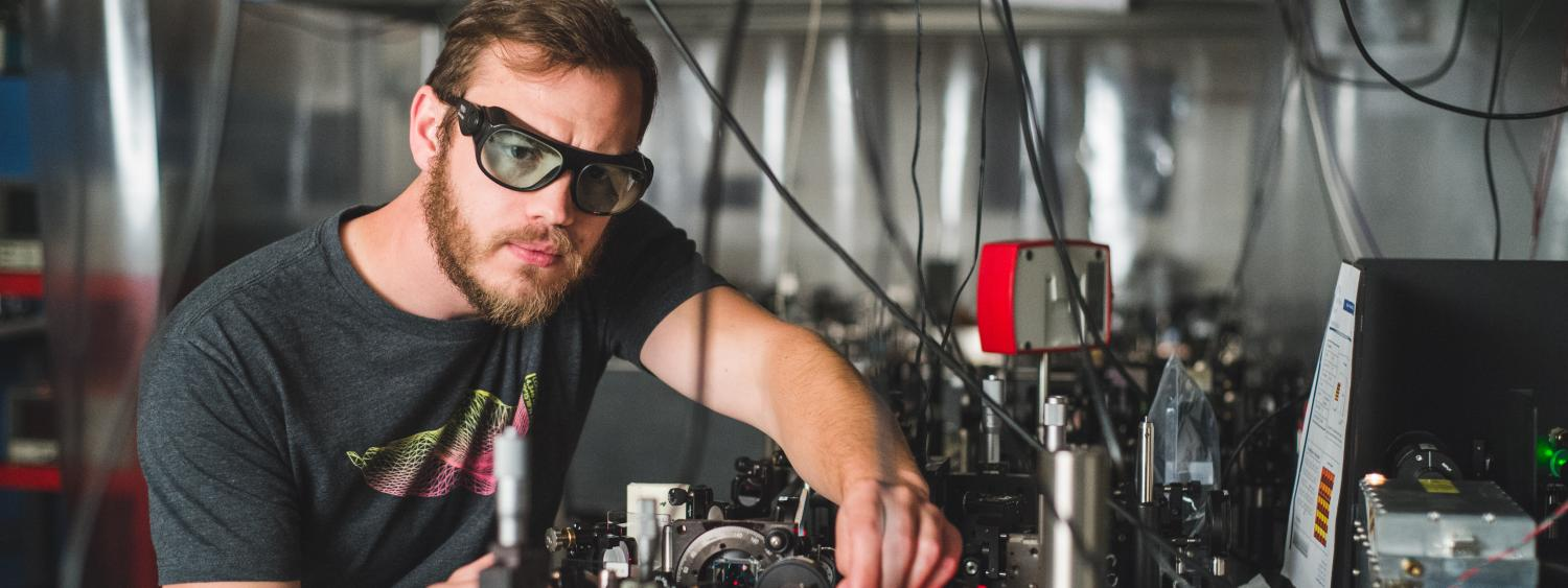 A student works at an optics table in a lab.