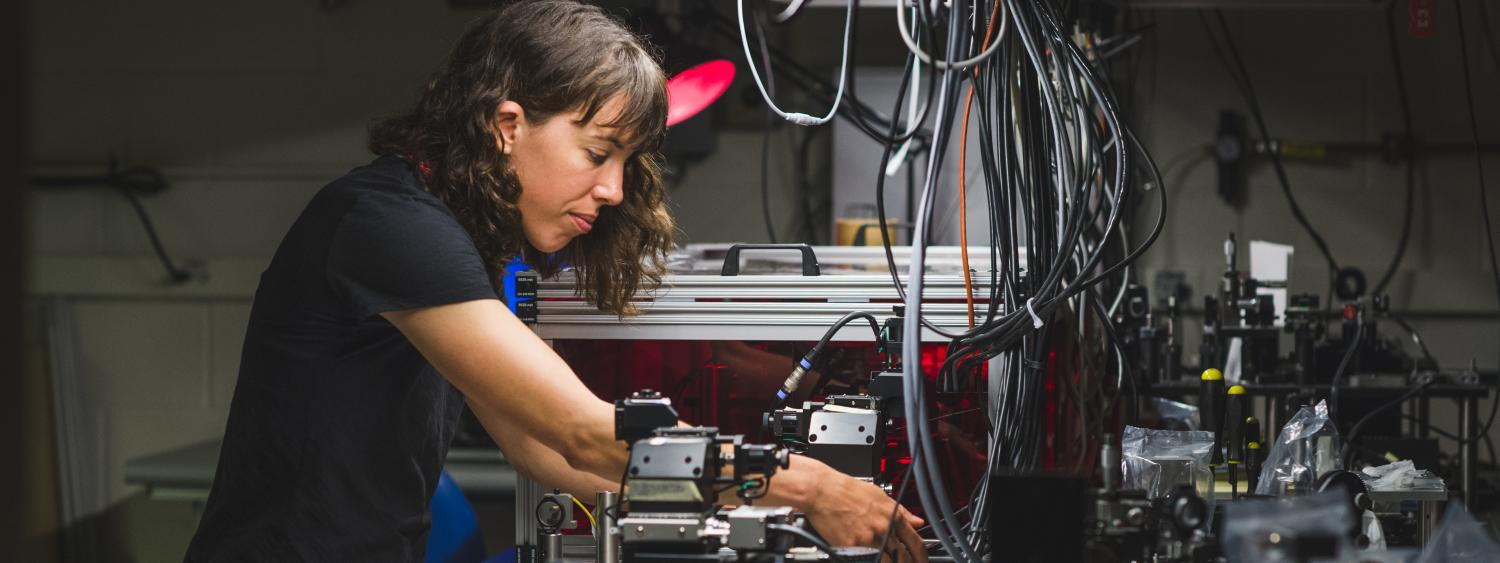 A grad student works on an optical project in her lab. Cropped photo.