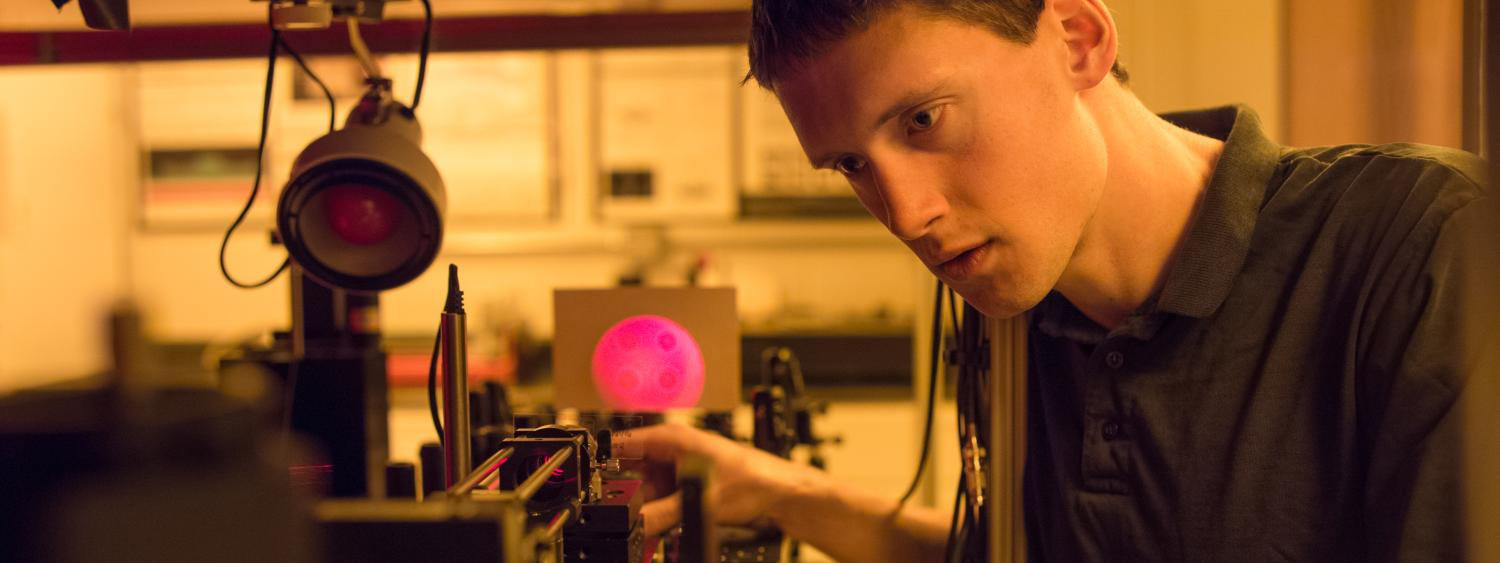 A graduate student works at a light table in a photonics lab.