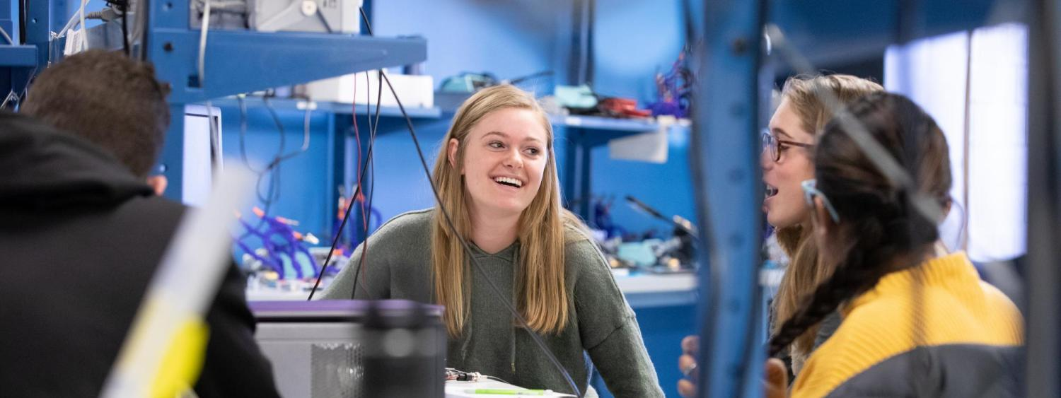 Students laugh together while working on a project during a lab session.