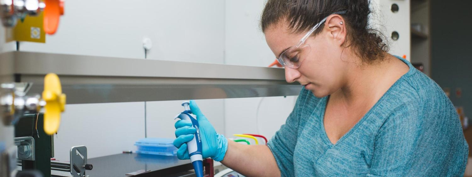 A grad student works at a fume hood in an optics lab.