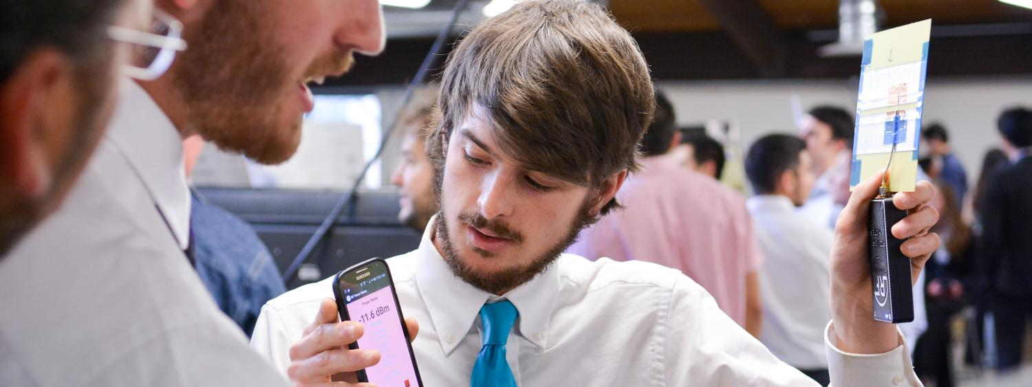 A student holds an antenna and smartphone while demonstrating his team's senior capstone project.