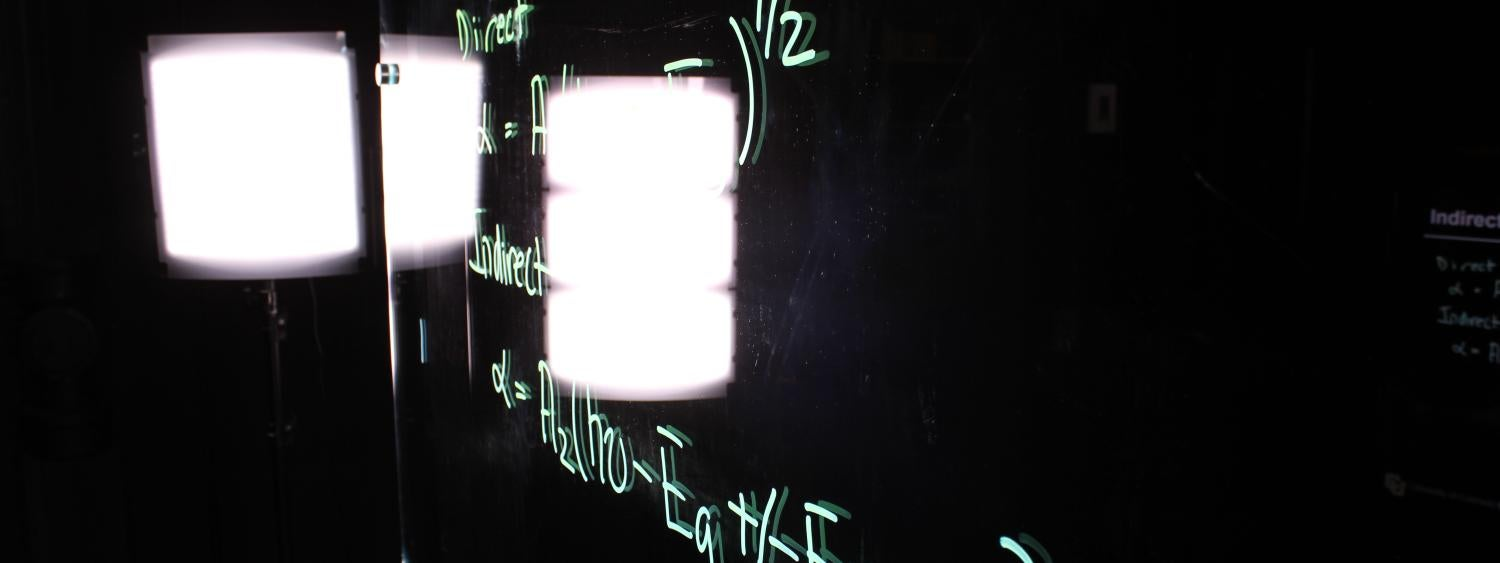 Handwritten equations on the lightboard with studio lighting in the background