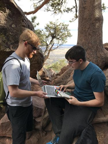 Alex Fosdick and a student look over some data on a laptop at the side of a trail