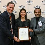 Pao receives her plaque from two colleagues during the ASME conference.