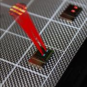 A silicon chip with a tiled array of serpentine optical phased array (SOPA) tiles. Drawn superimposed are beams from two matching tiles and the far field beam interference pattern demonstrating tiled beam forming.