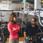 Juliet Gopinath and a grad student discuss a project at the optical table in their lab