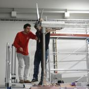Misha Sinner and a fellow student stand on scaffolding to work on a turbine model.