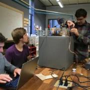 Three students troubleshoot their safecracking robot in the BTU Lab