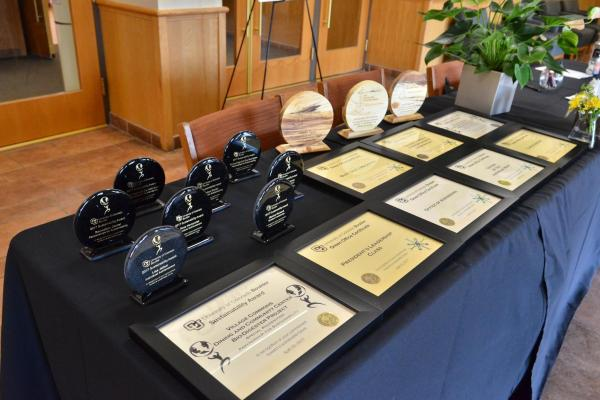 a table covered with award plaques and trophies
