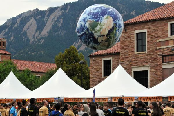 a globe balloon floats over a crowd on Farrand Field