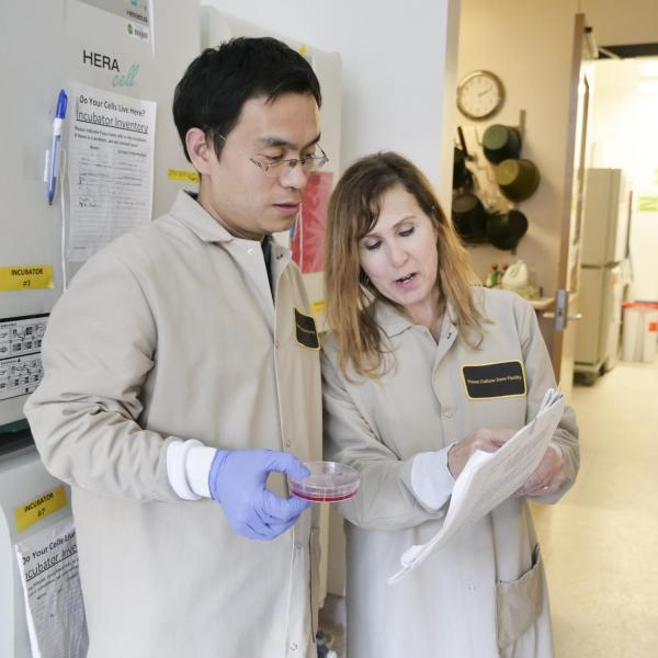 two scientists in lab coats confer