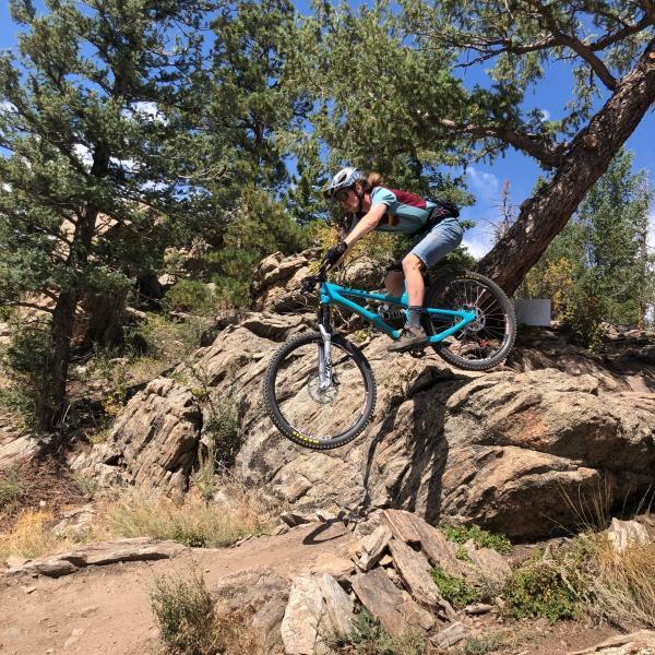 Jake riding his mountain bike over a Boulder.